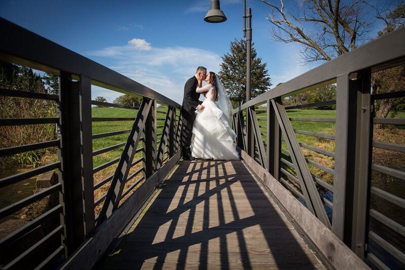 bride and groom kissing on wooden bridge