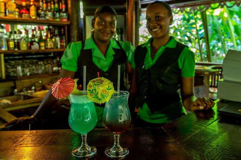 two bartenders with cocktails in tropical setting
