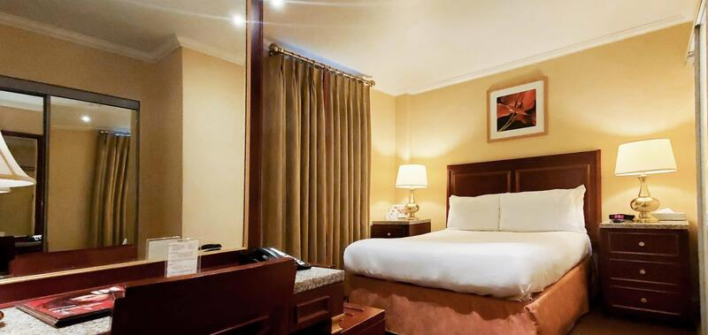 Queen bed in hotel room with desk