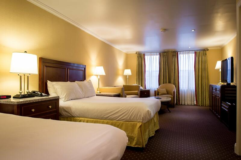 Two beds and seating area in hotel suite