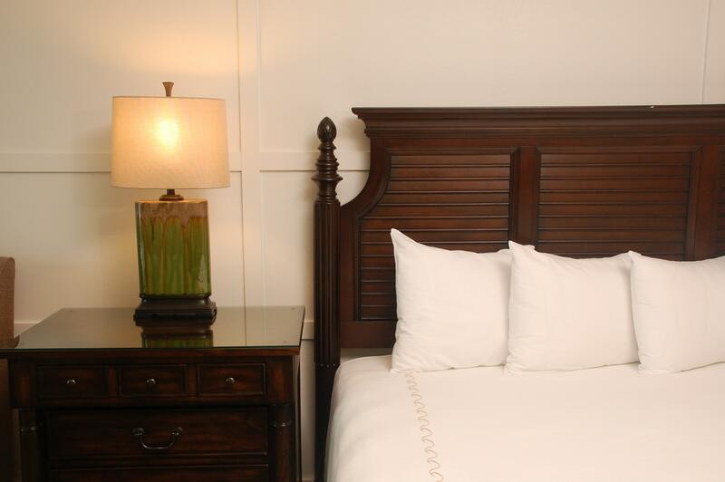 bed with white sheets and nightstand