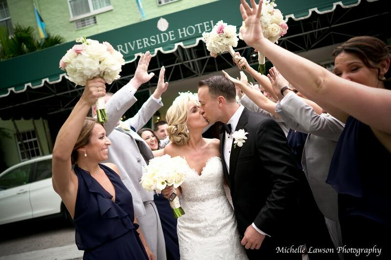 bride and groom kissing with people cheering