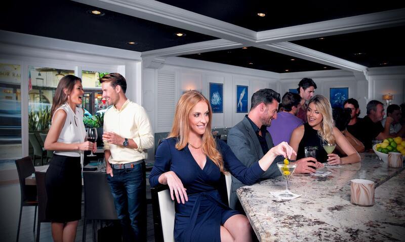 adults drinking martinis at bar