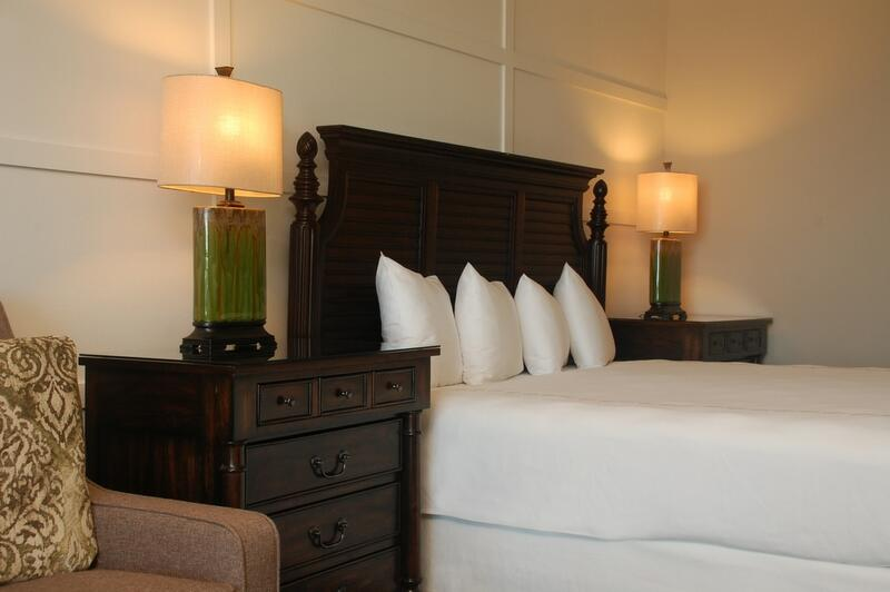 bed with white sheets and night stands
