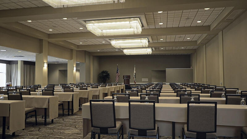 ballroom set with tables, chairs and projector for conference ev