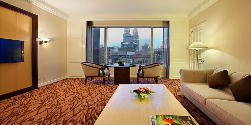 Living room of club suite furnished with sofas, TV and coffee ta