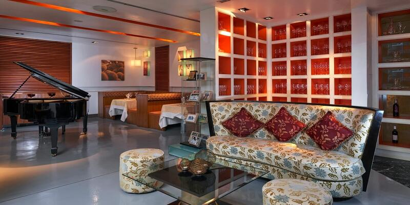 Restaurant furnished with couches and a piano