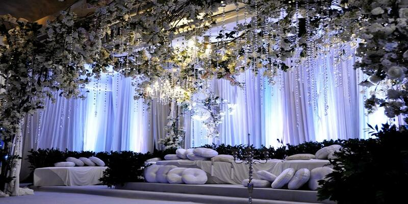Wedding set up that features white flowers, pearls and cushions