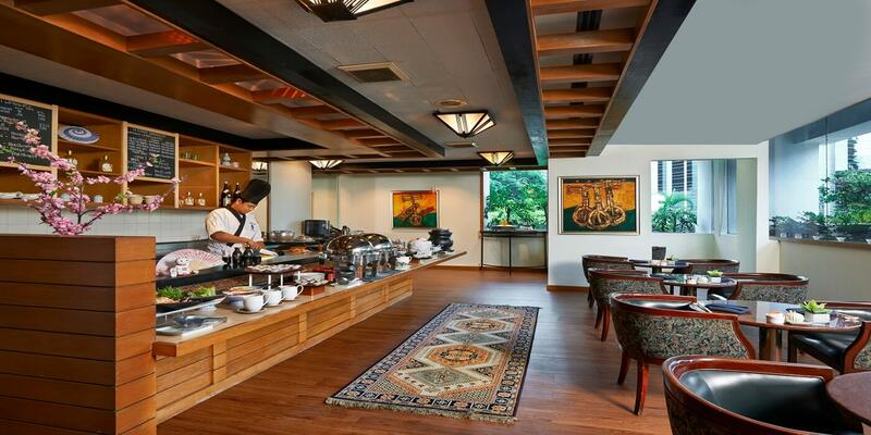 A dining lounge with live station where a chef is prepping food