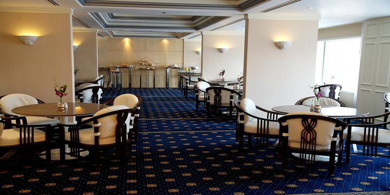 Dining area of club lounge furnished with round tables
