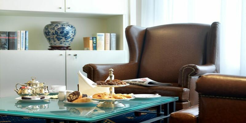 A leather armchair and coffee tables filled with pastries