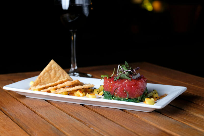 plate of ahi tuna and a glass of wine