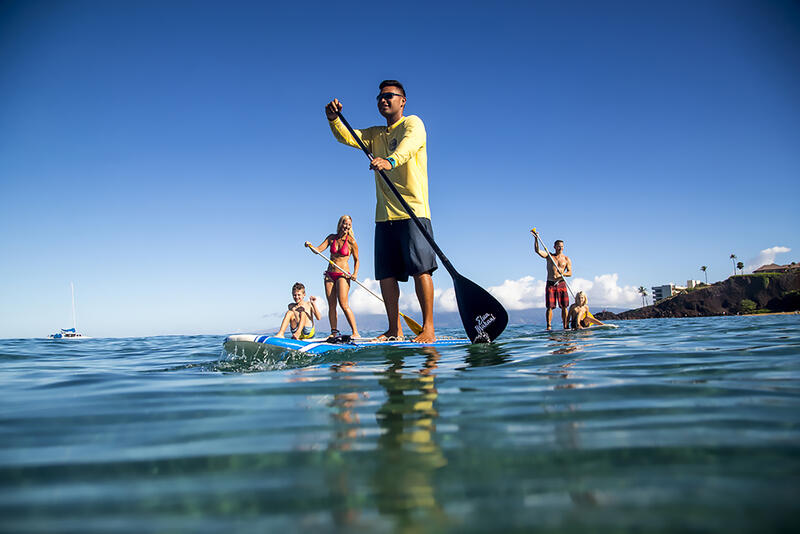 group of people paddleboarding in ocean