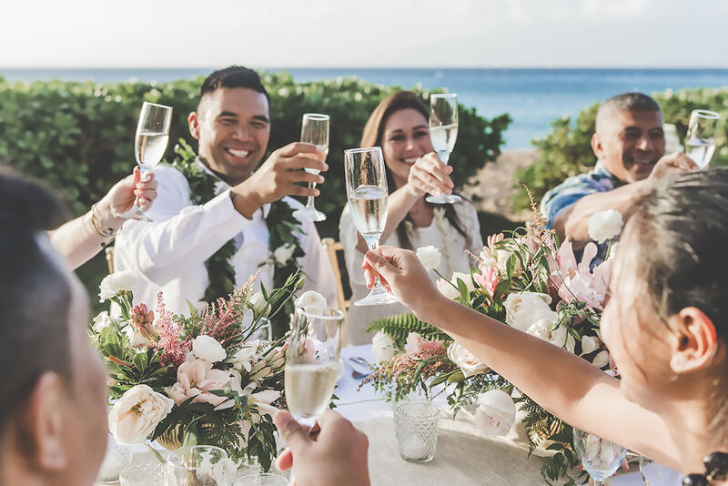 wedding party raising their glasses on beach