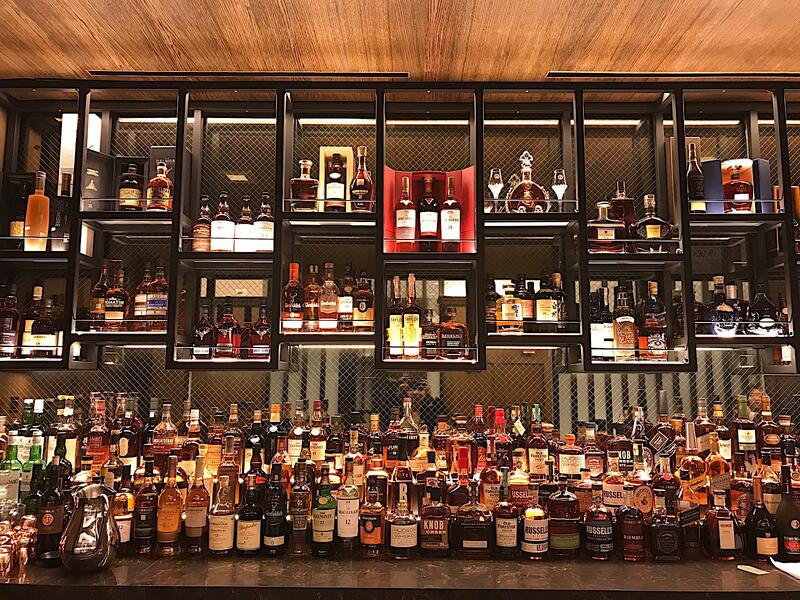 Multiple whiskey bottles at the bar