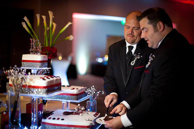 two men serving wedding cake