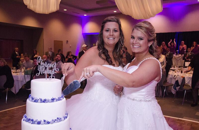 two woman cutting a wedding cake