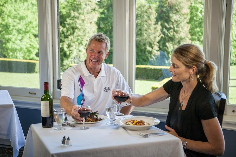 couple laughing at dining table with red wine