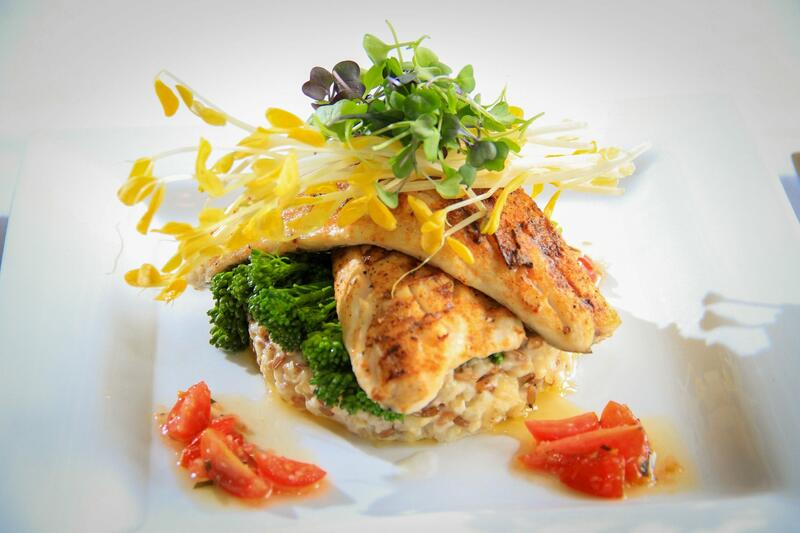 chicken breast on bed of potatoes and vegetables