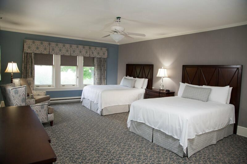 two beds with white sheets in carpeted room with window