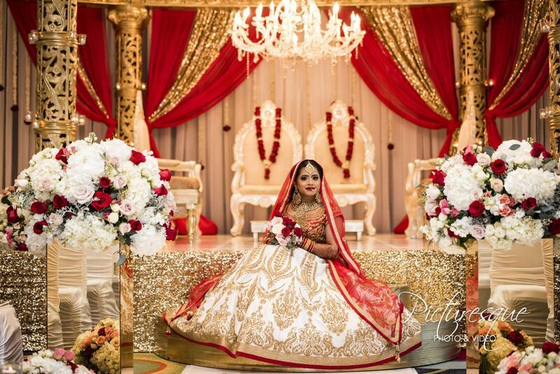 indian bride sitting on gold altar