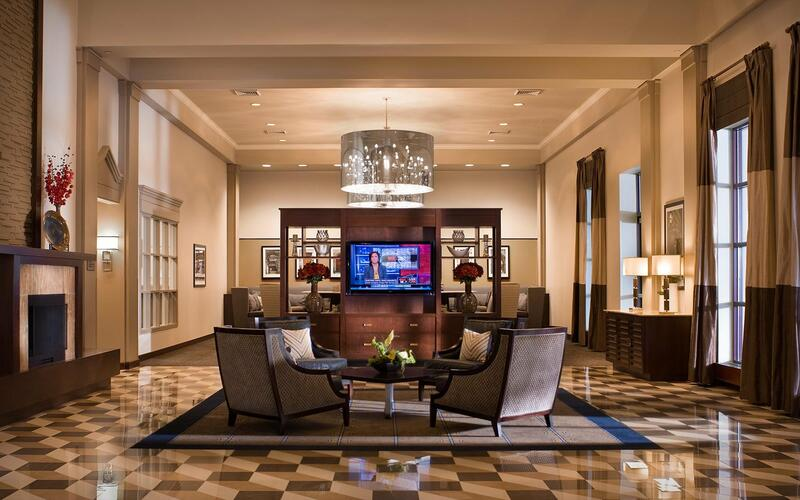 chairs facing a tv in a hotel lobby