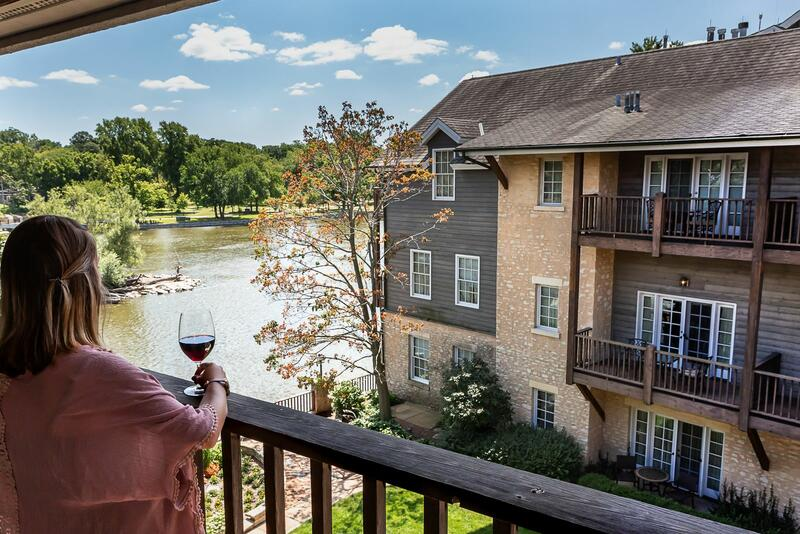 woman holding a glass of wine on a river