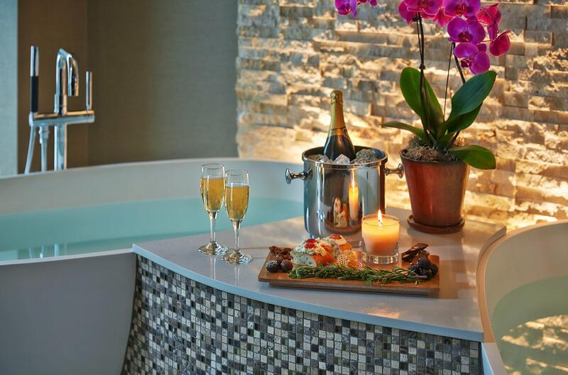 glass of wine and food by two bath tubs