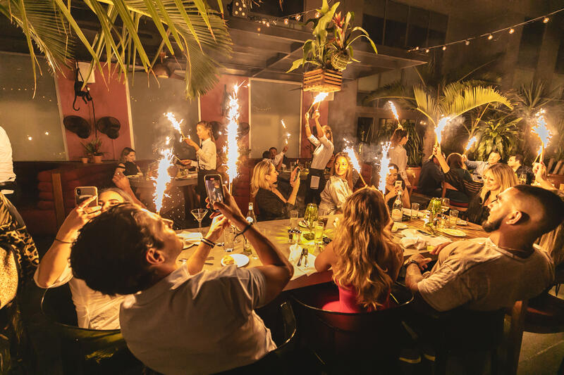 group of people at dinner table with sparklers