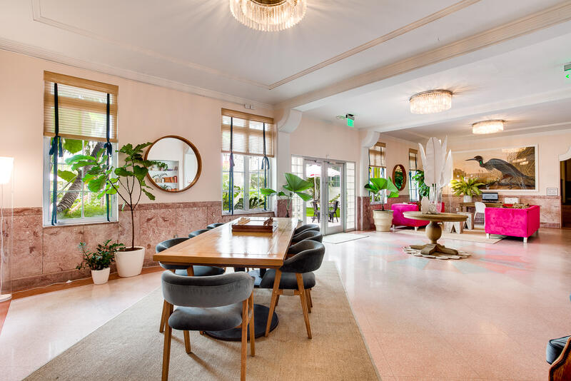 lobby with community table and pink sofas near entrance