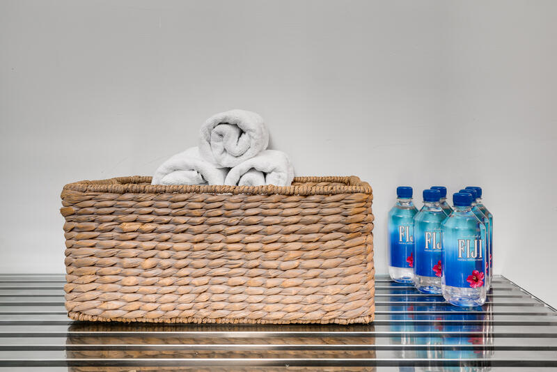 basket with rolled towels next to water bottles