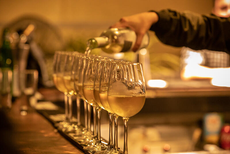 hand bouring wine into wine glasses