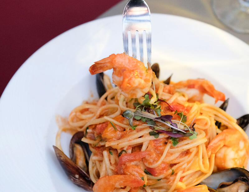 white bowl of seafood pasta being rolled onto fork