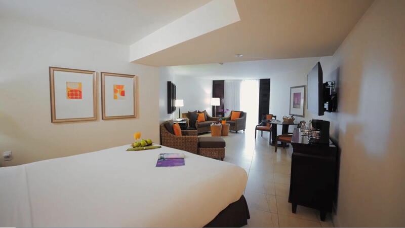 open room with king bed, television on wall and several seating