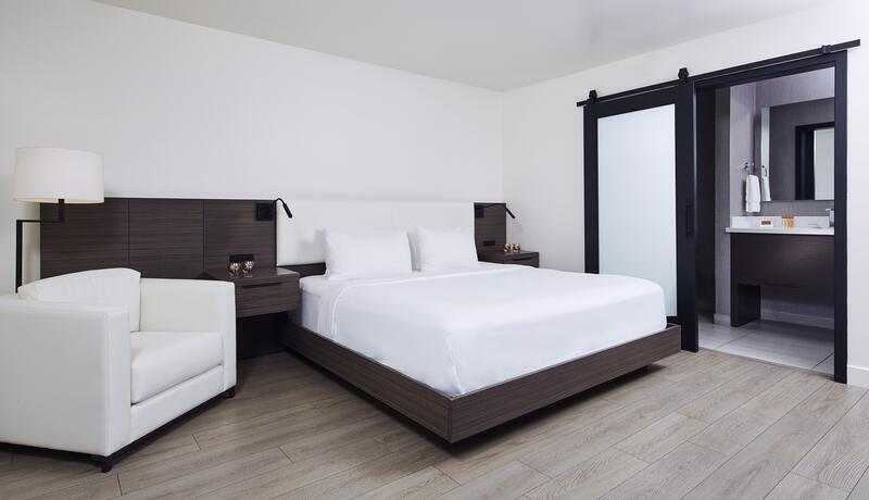 large king bed and a chair in a hotel room
