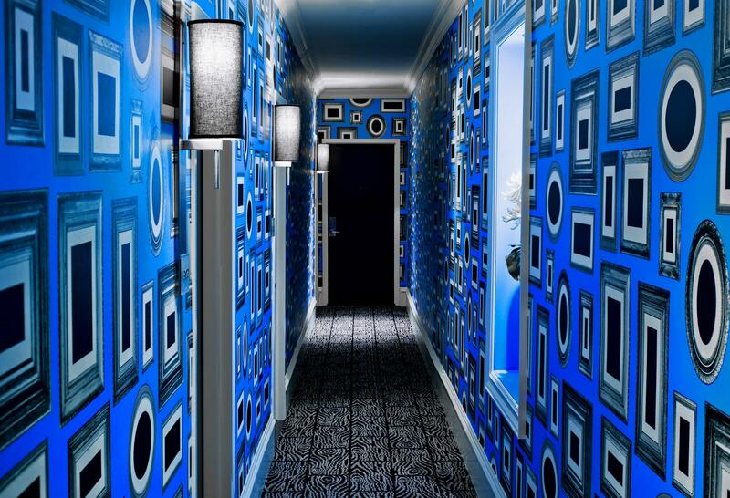 a hallway with vibrant blue wallpaper