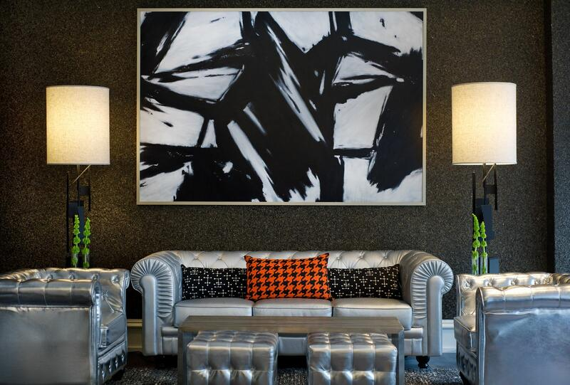 an abstract painting hanging above silver couches and chairs