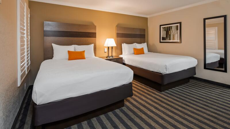 two beds and pillows in a hotel room