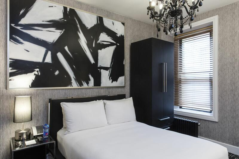 bed in a hotel room with a painting on the wall