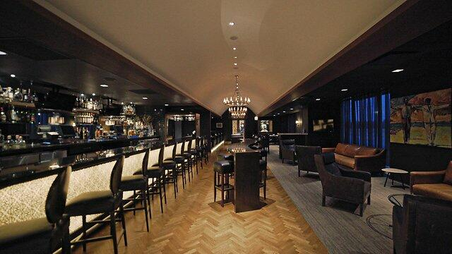 a long bar area with stools, chairs, and couches