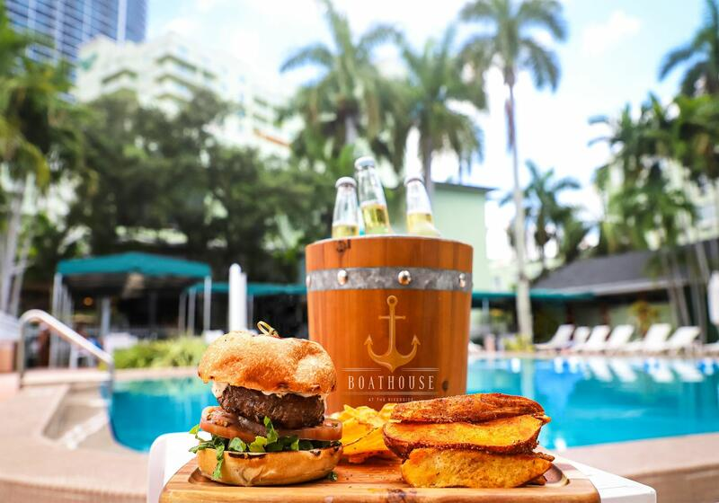 burger and fries next to pool with bucket of beers