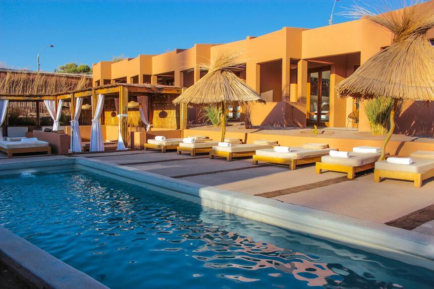 outdoor pool & chairs with umbrellas at NOI Casa Atacama Hotel