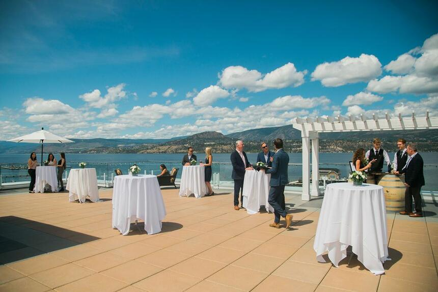 Outdoor terrace with standing cocktail tables and lake view.