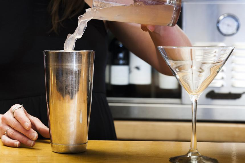 bartender pouring drink into mixer next to martini glass