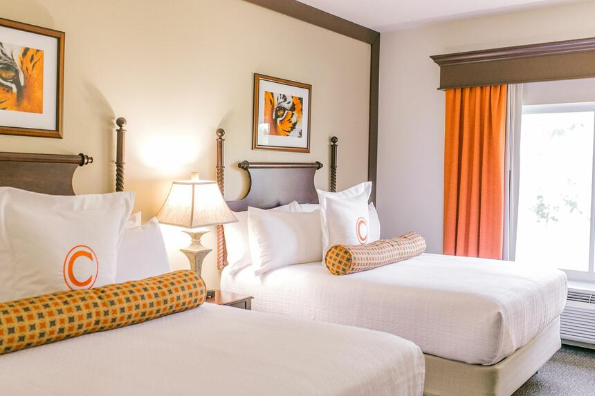 two double beds in hotel room with window and orange curtains