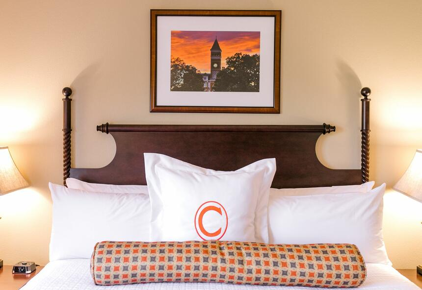 bed and pillow with the letter C and picture frame on the wall