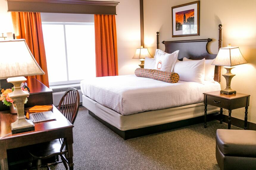 king bed in hotel suite with window and orange curtains