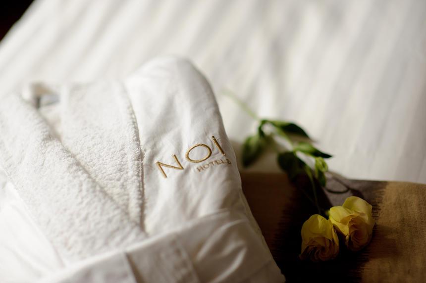 white folded bathrobe & 2 yellow roses at NOI Vitacura hotel