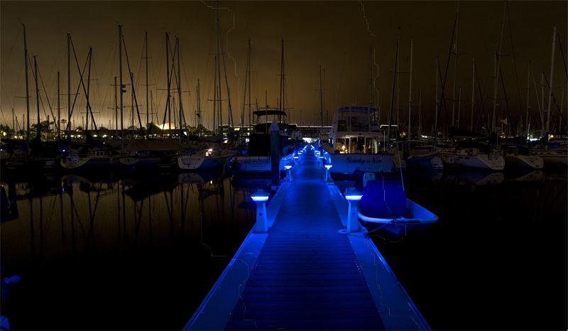 Blue lights outline a walkway leading to boats in a marina