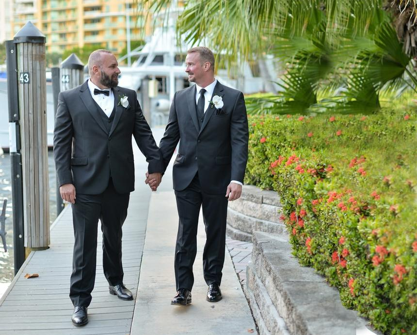 two bed in tuxedos holding hands